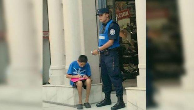 La emotiva imagen de un policía que ayuda a estudiar a un chico de la calle